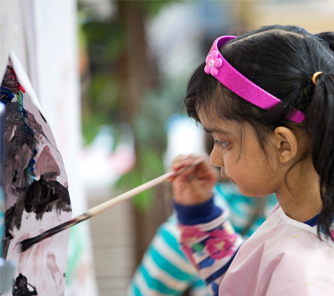 Young girl painting with a paintbrush